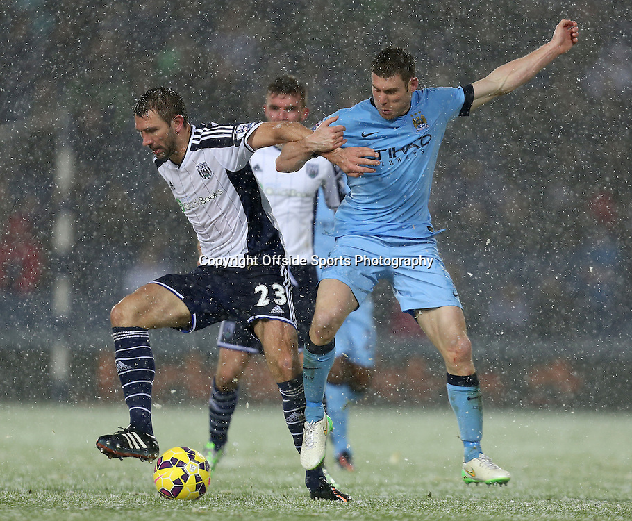 26th December 2014 - Barclays Premier League - West Bromwich Albion v Manchester City - Gareth McAuley of West Bromwich Albion and James Milner of Manchester City battle for the ball in the snow - Photo: Paul Roberts / Offside.