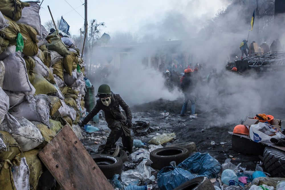 KIEV, UKRAINE - JANUARY 25: An anti-government protester climbs over trash to get a tire to burn during clashes with police on Hrushevskoho Street near Dynamo stadium on January 25, 2014 in Kiev, Ukraine. After two months of primarily peaceful anti-government protests in the city center, new laws meant to end the protest movement have sparked violent clashes in recent days. (Photo by Brendan Hoffman/Getty Images) *** Local Caption ***