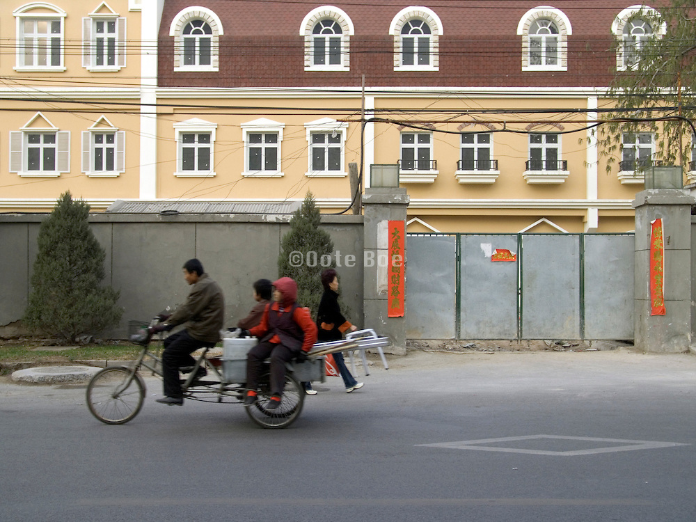father with children passing an new residential building complex under construction