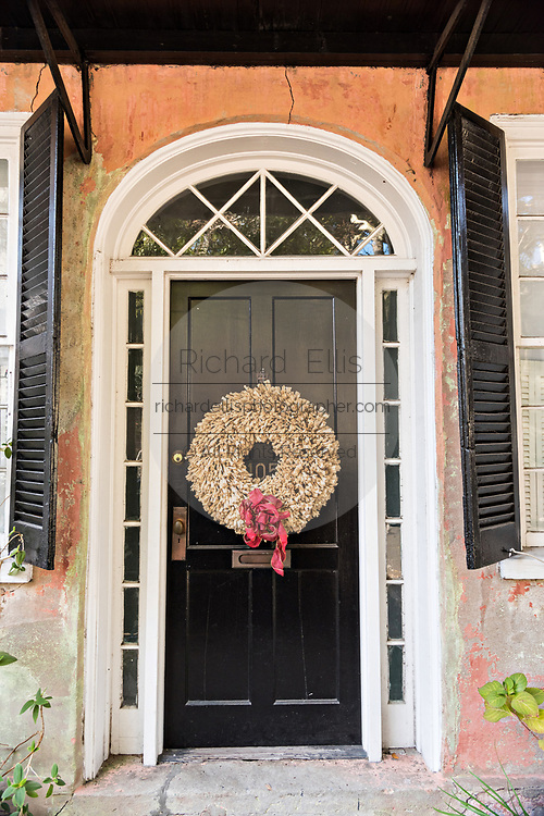 A wooden door of a historic home decorated with a Christmas wreath on Meeting Street in Charleston, SC.