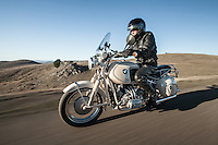 Brent Greenwood (MR) riding his 1960s BMW R60US motorcycle (PR) on a country road in Sonoma County California.