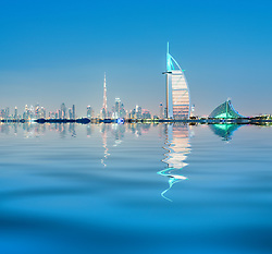 Night skyline across sea to luxury Burj al Arab hotel and city of Dubai with Burj Khalifa tower in distance in United Arab Emirates