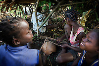 Kaga Bandoro, Central African Republic (CAR). Children under a cover of palm leaves are drumming on dried gourds. With the sound they try to imitate the drumming of heavy rain on the soil. The monsoon is about to arrive and they trick huge termites in coming up from their holes. The emerging insects are caught before they can fly away. They are collected in bowls. They will be used for dinner..The kids catch the occasional escapees in midflight and eat them right away. They provide a healthy and tasty snack. .