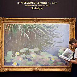 London, UK - 31 January 2013: A Sotheby's employee poses in front of a painting entitled 'Nymphéas avec reflets de hautes herbes' by Claude Monet (Est. £12-18 million) during the press preview of the forthcoming February sales of Impressionist & Modern Art and Contemporary Art in London, including works by Picasso, Bacon, Monet, Richter, Miró, Basquiat.