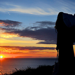Hiker contemplates the beautiful sunset of the Gower Peninsula, Wales, UK