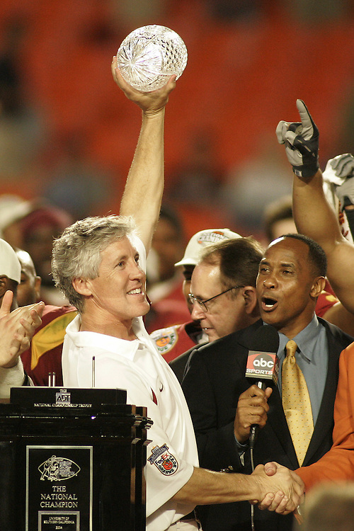 University of Southern California head coach Pete Carroll hold up the ADT championship trophy as USC alumnus Lynn Swann looks on after USC's 55-19 victory over Oklahoma on January 4, 2005 in the FedEx Orange Bowl at Pro Player Stadium in Miami, Florida.