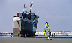 """BLANKENBERGE, BELGIUM - NOVEMBER 9, 2001 - A wind surfer sails by a stranded cargo ship on the beach at Blankenberge. The German cargo ship """"Heinrich Behrmann"""", was beached by heavy seas after losing power to the main engine late Thursday night at Blankenberge. The ship was heading for the port at Zeebrugge from Ireland, and was carrying dry cargo, none of which was hazardous. The salvage company Unie Van Redding - En Sleepdienst N.V. was hired to free the ship. Three unsuccessful attempts were made Friday, the second attempt resulted in the injury of two workers when tug boat cables snapped. The beached ship has attracted the attention of curious tourists. (Photo © Jock Fistick)"""