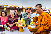 "22 JULY 2014 - BANGKOK, THAILAND: A Thai man makes merit by presenting alms to a Buddhist monk during a merit making ceremony at Sanam Luang. Hundreds of Thai military officers and civil servants attended a Buddhist chanting service and merit making ceremony to mark the 2nd month anniversary of the May 22 coup that deposed the elected civilian government and ended nearly six months of sometimes violent anti-government protests. The ruling junta said the ceremonies Tuesday were the kickoff to a ""Festival to Bring Back Happiness of the People of the Nation."" There will be free concerts, historical pageants and movies at Sanam Luang, a large parade ground near the Ministry of Defense in Bangkok.    PHOTO BY JACK KURTZ"