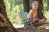 Girl Sitting on Deckchair in Forest