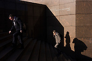 Surrounded by deep shadows, commuters climb the steps of number 1 London Bridge.