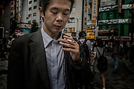 Man concentrates on his cigarette.  Shinjuku, Tokyo, Japan