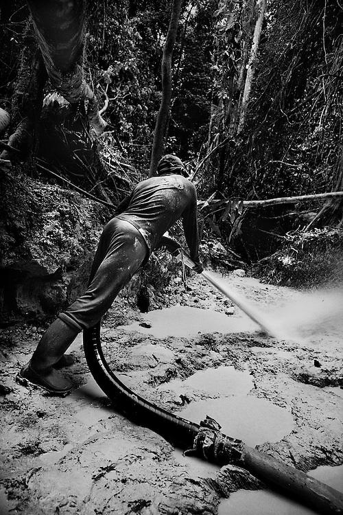 Guyane francaise, Yaou, concession miniere.<br /> <br /> Exploitation miniere clandestine sur la concession de la Societe Miniere Yaou Dorlin. <br /> A la suite de Guyanor en 1993, plusieurs societes investissent dans la prospection. L'or, une des rares exportations guyanaises, represente 264,9 MF en 1999 et emploie officiellement 900 personnes. Quelques multinationales gerent la majorite des sols, 200 km2 de titres sont attribues, on estime &agrave; 600 km2 la zone orpaillee clandestinement.<br /> Pompes et pelles mecaniques, les techniques et la main d&rsquo;&oelig;uvre sont bresiliennes. La terre est retournee et lavee a la recherche de paillettes qui seront amalgamees par addition de mercure.