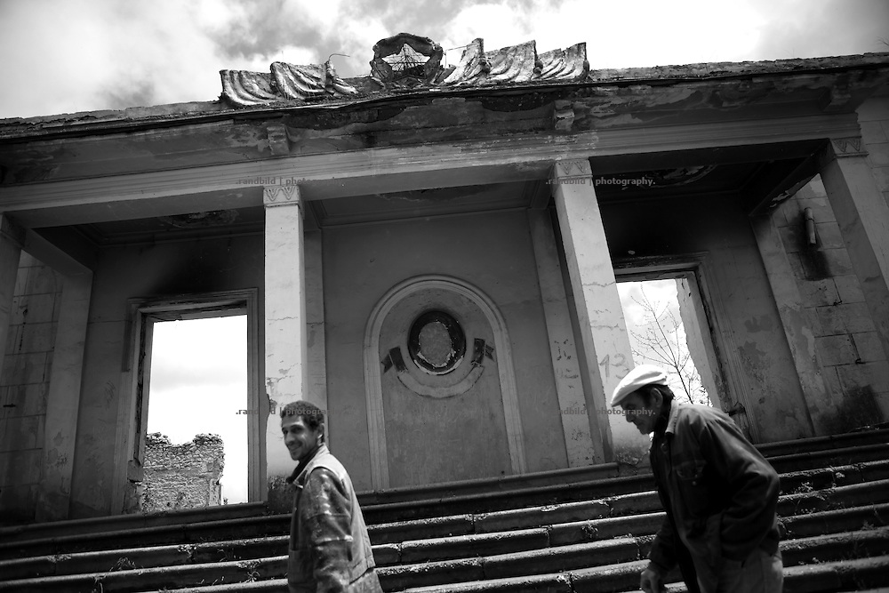 "Two men walk by a war damaged public house in Shushi. This image is part of the photoproject ""The Twentieth Spring"", a portrait of caucasian town Shushi 20 years after its so called ""Liberation"" by armenian fighters. In its more than two centuries old history Shushi was ruled by different powers like armeniens, persians, russian or aseris. In 1991 a fierce battle for Karabakhs independence from Azerbaijan began. During the breakdown of Sowjet Union armenians didn´t want to stay within the Republic of Azerbaijan anymore. 1992 armenians manage to takeover ""ancient armenian Shushi"" and pushed out remained aseris forces which had operate a rocket base there. Since then Shushi became an ""armenian town"" again. Today, 20 yeras after statement of Karabakhs independence Shushi tries to find it´s opportunities for it´s future. The less populated town is still affected by devastation and ruins by it´s violent history. Life is mostly a daily struggle for the inhabitants to get expenses covered, caused by a lack of jobs and almost no perspective for a sustainable economic development. Shushi depends on donations by diaspora armenians. On the other hand those donations have made it possible to rebuild a cultural centre, recover new asphalt roads and other infrastructure. 20 years after Shushis fall into armenian hands Babies get born and people won´t never be under aseris rule again. The bloody early 1990´s civil war has moved into the trenches of the frontline 20 kilometer away from Shushi where it stuck since 1994. The karabakh conflict is still not solved and could turn to an open war every day. Nonetheless life goes on on the south caucasian rocky tip above mountainious region of Karabakh where Shushi enthrones ever since centuries."