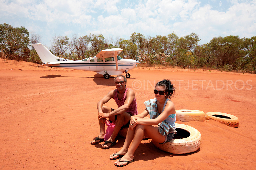 Father and daughter sitting on rubber tyres, waiting for the plane to leave, at the landing strip at Cape Leveque at Kooljaman at The Dampier Peninsula, North of Broome., WA