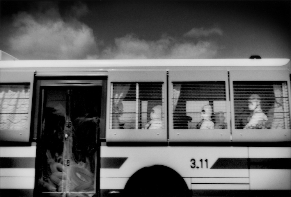 Recovery workers, probably police, wearing full-body white suits to protect them from radiation, enter the 20 km (12.4 miles) nuclear no-entry zone in a police bus at the main check point on Route 6, Minami Soma, Fukushima Prefecture, Japan.  Recovery workers enter the no-entry zone to search for the bodies of the missing but the danger of radiation exposure has greatly slowed their progress.