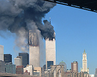The World Trade Center moments after the South Tower was struck by United flight 175. Fire had not yet spread throughout the floors and debris can be seen falling along the north façade. The Manhattan Bridge roadway frames the top of the scene.