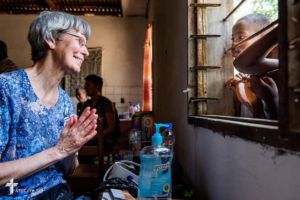 """Bonnie Hartman, a member of Faith Lutheran Church, Godfrey, Ill., gestures as she teaches the song """"Jesus Loves Me"""" to children outside her window on the first day of the LCMS Mercy Medical Team on Monday, May 7, 2018, in the Yardu village outside Koidu, Sierra Leone, West Africa. LCMS Communications/Erik M. Lunsford"""