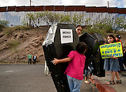 May 24, 2014, Nogales, Sonora, Mexico:  Protesters at the Victimas de la Patrulla Fronteriza Protest vigil in Nogales, Sonora, Mexico, were joined by protesters from the Border Patrol Victims Network from Nogales, Arizona, USA, along the international border in Sonora to support and unite families of those who have been killed or injured in incidents involving U.S. Border Patrol agents.  Alexa Marquez, 7, (center), carries a mock paper coffin near the international border wall.