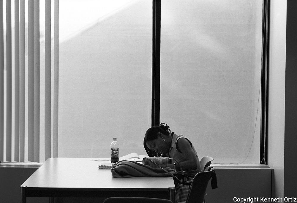 A young woman studying in the Hunter College Library.