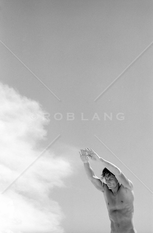 shirtless man diving into a cloud