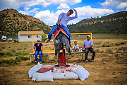 14 JULY 2012 - OAK SPRINGS, AZ: A bull riding student works out a mechanical bucking machine during a bull riding class in Oak Springs, AZ. The bull riding class was offered by the Crooked Horn Cattle Co. in the community of Oak Springs on the Navajo Nation, about 15 miles south of Window Rock, AZ. Eleven cowboys signed up for bull riding classes and one signed up for bull fighting classes. The bull riding class started with lessons on a mechanical bucking machine before the cowboys rode bulls.    PHOTO BY JACK KURTZ