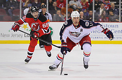 Feb 27, 2014; Newark, NJ, USA; Columbus Blue Jackets center Brandon Dubinsky (17) skates with the puck while being chased by New Jersey Devils right wing Jaromir Jagr (68) during the second period at Prudential Center.