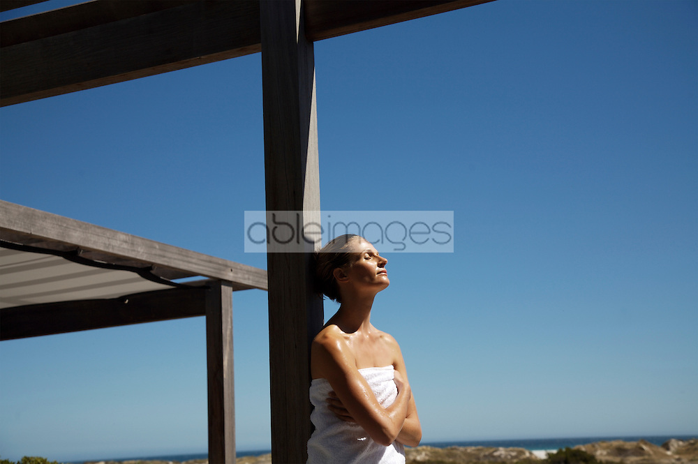 Woman wearing towel leaning against wooden beam relaxing and feeling sun warmth