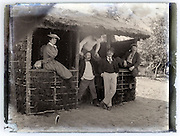 group of people posing by a hut vintage eroding glass plate