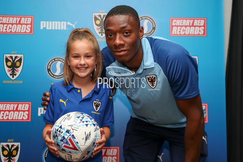 AFC Wimbledon defender Paul Kalambayi (30) with Mascot during the EFL Sky Bet League 1 match between AFC Wimbledon and Accrington Stanley at the Cherry Red Records Stadium, Kingston, England on 17 August 2019.