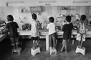 Nach dem Essen muessen die Kinder zum Kuechendienst und den Abwaschen machen. Provinz Lop Buri, Thailand..After having dinner, the kids have to clean the dishes in the kitchen........
