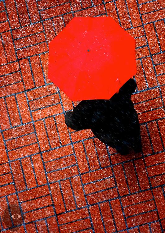 A heavy hail storm falls on downtown Portland and a pedestrian hiding beneath a red umbrella.