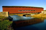 red covered bridge spanning blue water; rustic