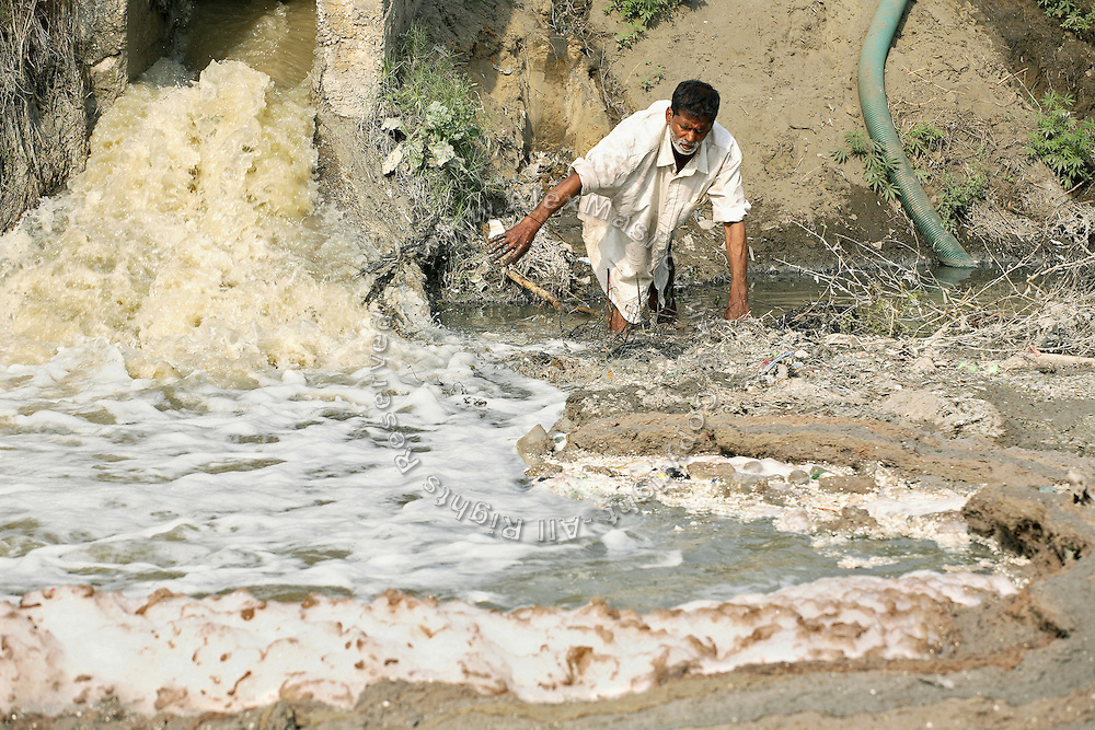 Pratap Singh, 52, a farmer from the village of Saini, pop. 4000, Meerut District, Uttar Pradesh, India, is portrayed while cleaning the way to his irrigation pump next to a paper mill drain flowing directly into the Kali river (East) waters, on Wednesday, Mar. 19, 2008. Pratap laments that the groundwater he was using for irrigation until one year ago has now finished and accuses the local industries to be taking it all for manufacturing products while discharging severely contaminated and untreated waters back into the environment. Not even after the monsoon season the village aquifers are able to fully recharge.