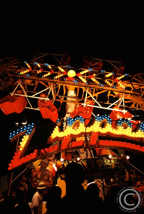 A bright fairground ride all lip up in neon.