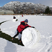 Simon Healy, 11 (front) and his brother Nicholas, 7, from Auckland,  use all their effort to make large snowballs at the Events Centre Fields, Queenstown, after fresh winter snow falls. Queenstown, Central Otago, South Island, New Zealand. 10th July 2011. Photo Tim Clayton..