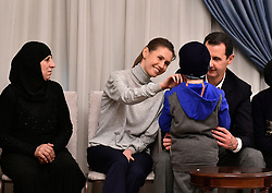 File photo - President Bashar al-Assad and his wife Asma received on Thursday tens of women and children who were released after they had been abducted from their villages in Lattakia countryside by the opposition forces for more than three and a half years. Damascus, Syria, February 9, 2017. Syria's British-born first lady Asma Assad has begun treatment for breast cancer. The Syrian presidency posted on its Facebook page a photo of President Bashar Assad sitting next to his wife in a hospital room. Photo by Syrian Presidential Press Office via SalamPix/ABACAPRESS.COM