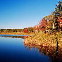 A calm lake in the fall surrounded by colorful leaves. Connecticut, USA.