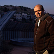 Sami Awad, executive director of Holy Land Trust stands in front of the border wall in the West Bank.  [WILLIE J. ALLEN JR.]