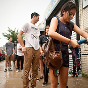 July 29, 2011 - Brooklyn, NY : Fernanda Rosas, who is from Cancun, Mexico, wrings out a wet garment after a torrential downpour as she  waits in line to enter the House of Vans at 25 Franklin Street in Greenpoint, Brooklyn on Friday night. Acts included the hardcore punk bands the 'Cro-Mags' and 'Fucked Up.' CREDIT: Karsten Moran for The New York Times