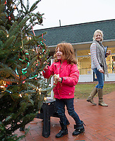 Tricia Poehler looks on as her daughter Stevie-Lynn helps decorate the Christmas tree in Meredith Park with homemade ornaments as part of the Greater Meredith Program on Saturday afternoon.   (Karen Bobotas/for the Laconia Daily Sun)