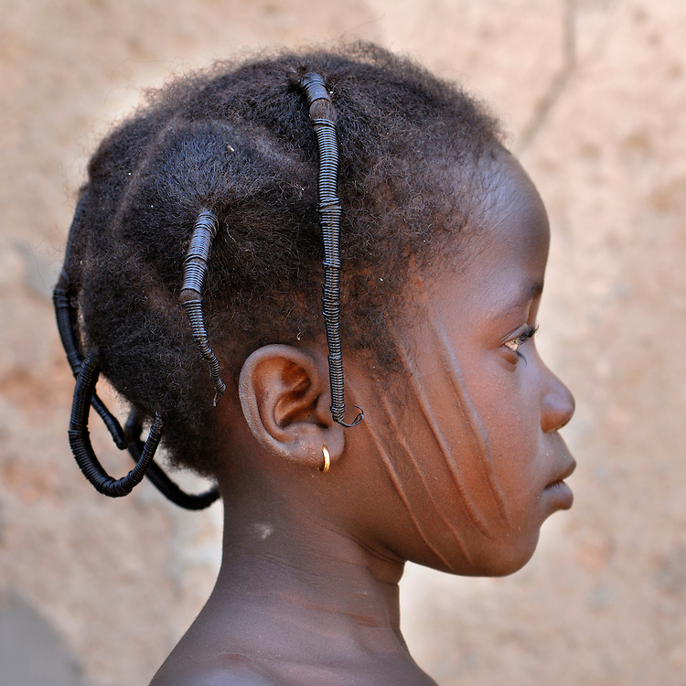 Benin, Natitingou November 26, 2006 - A young girl shows her facial scars which represent the Prince of Djougou, a small city in the center of Benin. Scarification is used as a form of initiation into adulthood, beauty and a sign of a village, tribe, and clan.