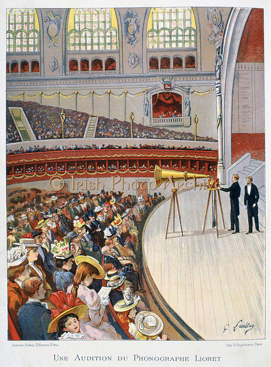 Demonstration on the stage of a crowded auditorium of Henri Lioret's weight-driven cylinder phonograph mounted on a tripod, c1898.  Sound Recording Technology Invention