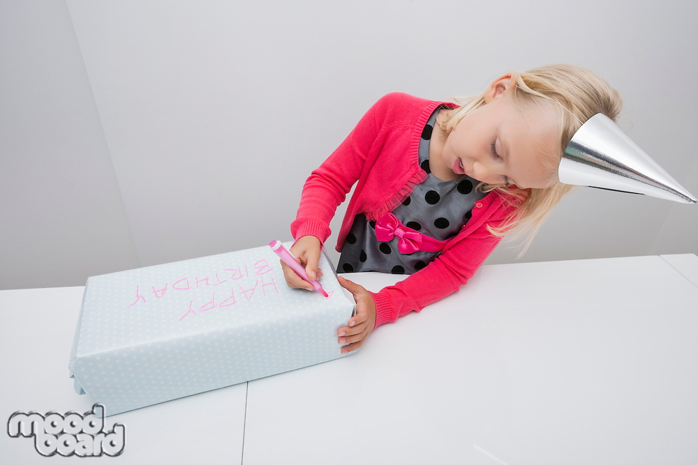 Cute girl writing on birthday gift at table in house