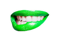 Close-up of teeth biting green lip over white background