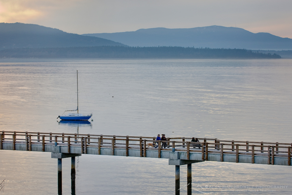 Sailboat anchored in Bellingham Bay  with the boardwalk of Boulevard Park in the foreground, the San Juan Islands are in the distance, Bellingham Washington USA