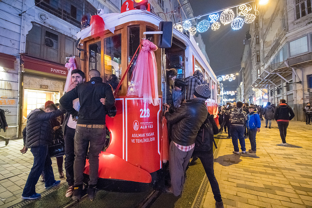 Passengers hang onto the sides of crowded trolley car as it makes it way through the streets of Istanbul, Turkey