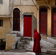 Medina, Tangier, Morocco pictured on December 18, 2009. An atmospheric view a man in traditional red Djellaba walking past the walls, doors and windows at haphazard angles in a corner of the old town.Tangier, the 'White City', gateway to North Africa, a port on the Straits of Gibraltar where the Meditaerranean meets the Atlantic is an ancient city where many cultures, Phoenicians, Berbers, Portuguese and Spaniards have all left their mark. With its medina, palace and position overlooking two seas the city is now being developed as a tourist attraction and modern port. Picture by Manuel Cohen