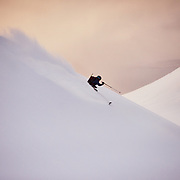 Claude skiing the ridge to Karlsárdalur Valley with the Atantic Ocean in the background at sunset