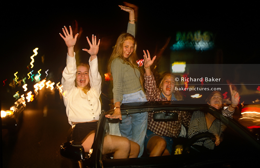 Young women whoop and cheer their favourite baseball team The Atlanta Braves' World Sreies win while out in the car.