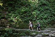 Adventurous walkers negotiate moderate terrain in the rocky gorge near the 15m high Kozjak Waterfalls, part of the Kobarid Heritage Trail, on 21st June 2018, in Kobarid, Slovenia.